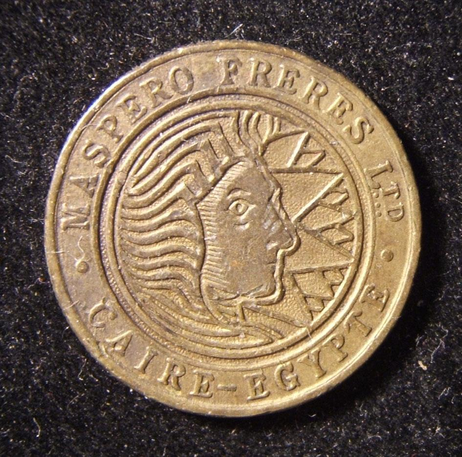 Egypt: Maspero Brothers Cigarette company bronze token, circa. 1930s; not maker-marked; size: 22.75mm; weight: 4.55g. Obv.: stylized face set against the sun(?); French legend