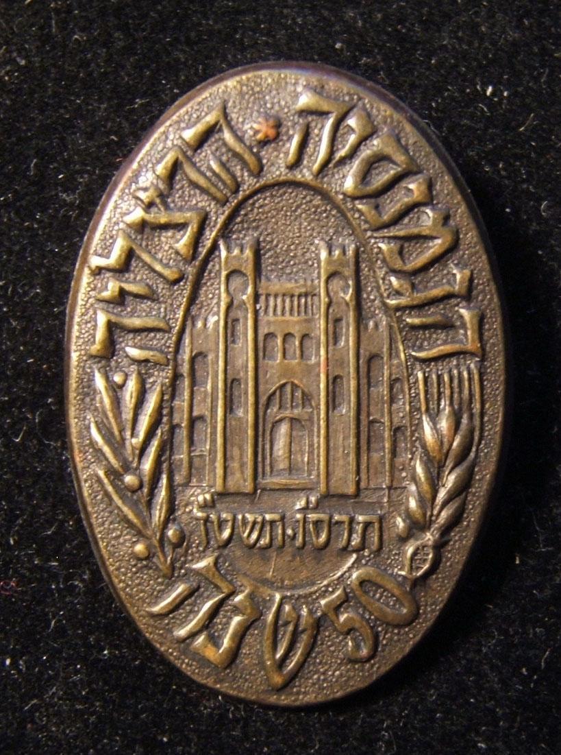 """Gymnasia Herzliya"" المدرسة الثانوية 50th الذكرى بيضاوي دبوس ، 1955 (بعد السنة اليهودية الجديدة 5716) ؛ الحجم: 20 × 28 مم. الوزن: 2.7g. يصور المبنى الأصلي مع غمد القمح"