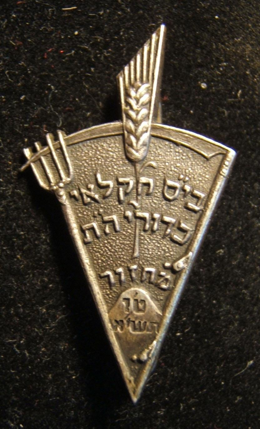 Palestine/Yishuv: Kadoorie Agricultural High School 15th student year pin, 1940-41; not maker-marked; size: 18 x 31.5mm; weight: 3.2g. The pin is wedge-shaped and formed from the c