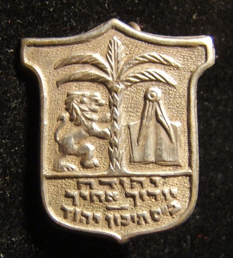 Israel: Yahud High School pin, circa. 1963; not maker-marked; size: 18 x 21mm; weight: 1.6g. Obverse depicts the coat of arms of the city of Yahud, with a contraction of the city's