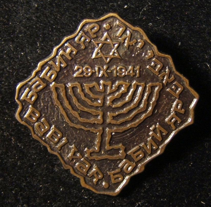 Pin commemorating the Babi Yar massacre, circa. 1961; size: 26x26mm; weight: 6.75g. In English, Hebrew, Russian and Ukranian.