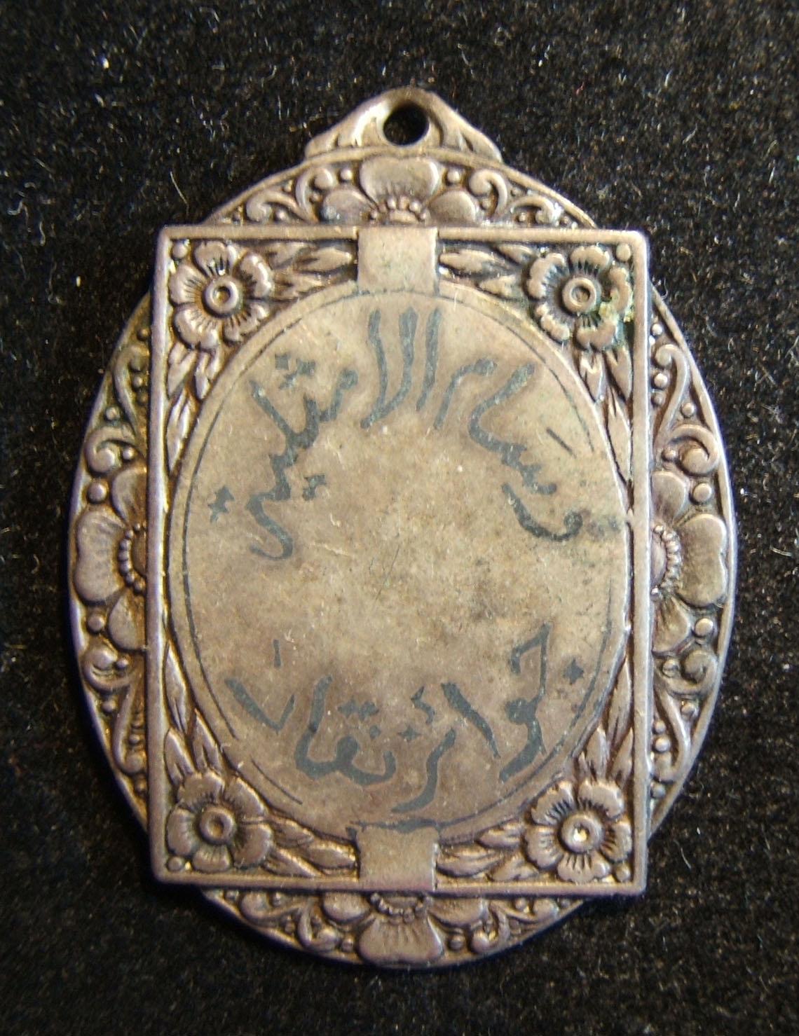 Jordan(?): ornate award in white metal (silver?); size: 26.5 x 35 mm; weight: 4.5g. Obverse legend, paint on metal: