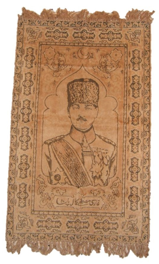 Turkey(?): Mustafa Kemal [Atatürk] carpet, circa. 1920-1923; size: carpet only (not fringes): 59.7cm x 95.7cm. Based on 1918 photo of Ataturk, although carpet's rendition more yout