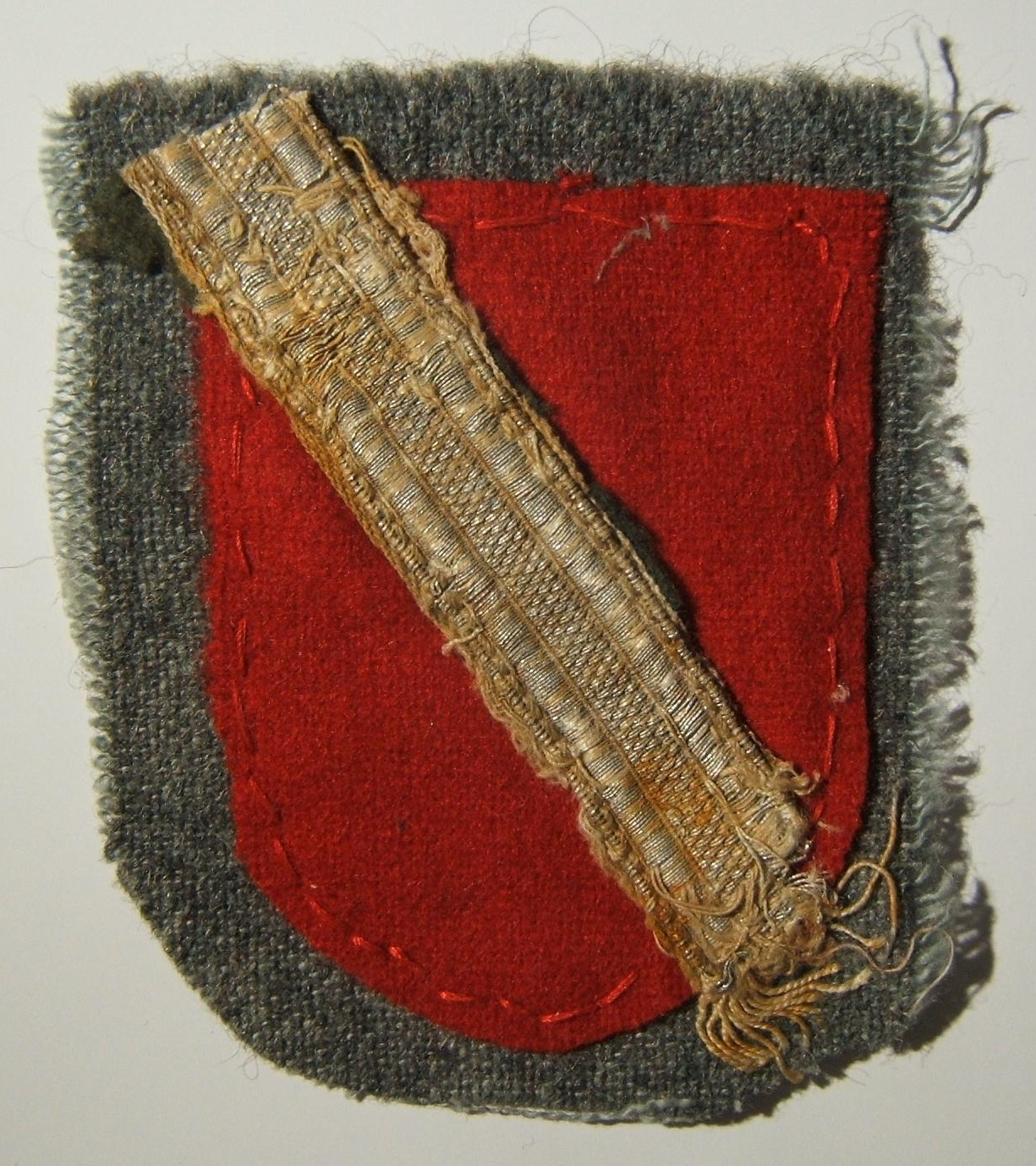 Handmade armshield of a Cossack force of the Wehrmacht: red cloth shield with diagonal silver tress across the field, still attached to the original 'waffenrock' swatch of the wear