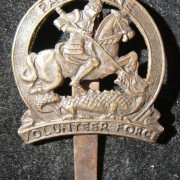 Palestine Volunteer Force metal hat insignia badge, circa. 1940-1943; not maker-marked; with slider back; weight: 4.75g. Depicts patron saint St. George slaying a dragon (i.e. Nazi