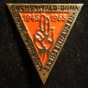 Triangular colored commemoration pin for 20 years to the liberation of Buchenwald-Dora, Ravensbruck and Sachsenhausen concentration camps, 1965; size: 28 x 30mm; weight: 2.2g.