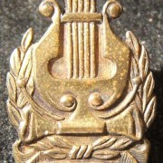 Tunic pin of the IDF Orchestra with screw-back, circa. 1950's-60's; size: 16 x 22.5mm; weight: 2.4g. Emblem depicts David's Lyre with two olive branches and Hebrew legend
