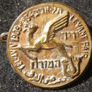 Palestine/Yishuv: Trilingual pin of the 1934 Levant Fair held in Tel Aviv, also commemorating the city's 25th anniversary featuring the fair's emblem of the flying camel and the ci